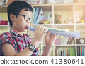 Boy playing the clarinet, trumpet at home,  41380641