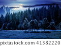 double moon over the forested landscape at night 41382220