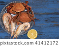 Cooked prawns and crabs on blue plate with Lemon 41412172