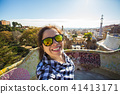 Young happy woman making selfie portrait with smartphone in Park Guell, Barcelona, Spain. Beautiful 41413171