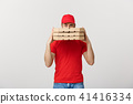 A Deliveryman hidden behind a large stack of pizza boxes he is carrying. Isolated over grey 41416334