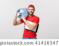 Handsome young delivery worker in red uniform is holding a bottle of water, looking at camera and 41416347
