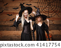 Halloween Concept - cheerful mother and her daughter in witch costumes celebrating Halloween posing 41417754
