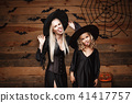 Halloween Concept - cheerful mother and her daughter in witch costumes celebrating Halloween posing 41417757