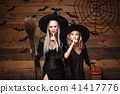 Halloween Concept - cheerful mother and her daughter in witch costumes celebrating Halloween doing 41417776