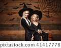 Halloween Concept - cheerful mother and her daughter in witch costumes celebrating Halloween posing 41417778
