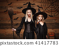 Halloween Concept - cheerful mother and her daughter in witch costumes celebrating Halloween posing 41417783