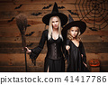 Halloween Concept - cheerful mother and her daughter in witch costumes celebrating Halloween posing 41417786