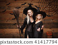 Halloween Concept - cheerful mother and her daughter in witch costumes celebrating Halloween posing 41417794