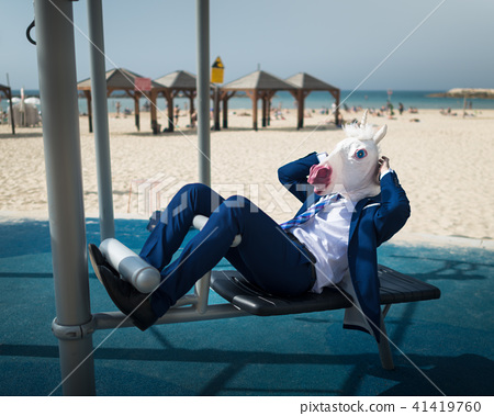 Freaky man in suit and funny mask is doing sport  41419760