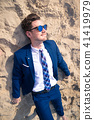 Funny young man in elegant suit lies on the beach. 41419979