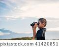 Happy kid playing binoculars in the meadows. 41420851