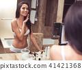 Joyful female applying cream before make up 41421368