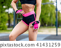 Woman in bright sportswear posing on sports ground. 41431259