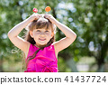 The girl is playing with big sweets on a stick. 41437724