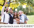 Bride, groom and guests with smartphone taking selfie outside at wedding reception. 41438897