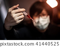 Young man using syringe for red drug injection 41440525