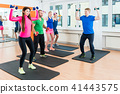 Men and women in gym doing pilates workout 41443575