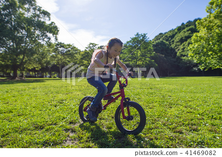 A girl playing with a bicycle 41469082