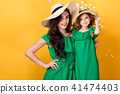Young woman with hand on waist standing with small daughter 41474403
