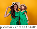 Young woman with hand on waist standing with small daughter 41474405