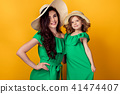 Young woman with hand on waist standing with small daughter 41474407