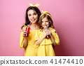 Beautiful mother with daughter drinking through straw 41474410