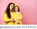 Young woman with cute child posing in yellow dresses 41474415