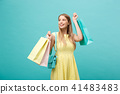 Shopping Concept: Portrait of an excited beautiful girl wearing yellow dress holding shopping bags 41483483