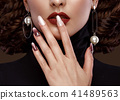 Pretty girl with unusual hairstyle, bright makeup, red lips and manicure design. Beauty face. Art 41489563