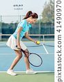 Professional female player smiling while serving during tennis match 41490970