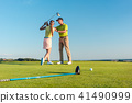 Golf instructor teaching a young woman to swing the driver club  41490999