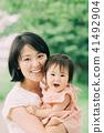 抱著嬰孩的一個年輕母親 41492904