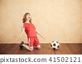 Child is pretending to be a soccer player 41502121