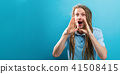 Young man shouting on a solid background 41508415