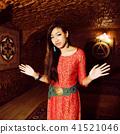 young pretty asian girl in bright colored interior on carpet. li 41521046
