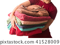 Woman holding stack of clean laundry towels. 41528009