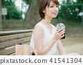 喝在長凳的婦女被冰的咖啡 41541304