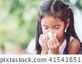 Sick girl wiping and cleaning nose with tissue 41541651