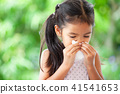 Sick girl wiping and cleaning nose with tissue 41541653