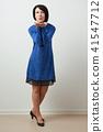woman posing in blue dress, makes a kiss 41547712