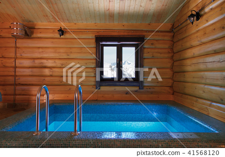 The interior of the traditional bath of wood is a pool and a hanging bucket. 41568120