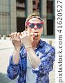 Stylish hippy man wearing bright headband playing the harmonica 41620527
