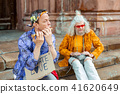 Man wearing shining jacket and floral headband playing the harmonica 41620649