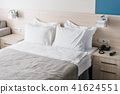Modern double bedroom. Comfortable soft white pillows on a bed. Inside rooms of a apartment or hotel 41624551