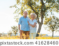 Romantic senior couple holding hands while walking together in the countryside 41628460