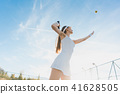 Woman serving the ball for a game of tennis 41628505