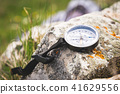 A magnetic compass lies on a stone next to the grass 41629556