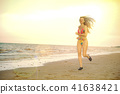 Attractive woman runs on sand beach in summer. 41638421