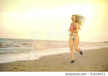 Attractive woman runs on sand beach in summer. 41638421